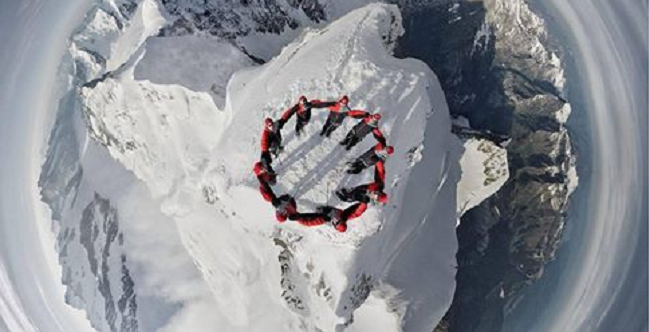 Amazing Drone Photo of Nine Mountain Climbers atop a Swiss Mountain Peak