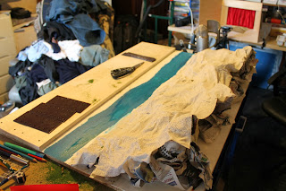 Photograph of a hilly model set with stream being built on a workshop table.