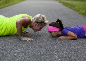 Mother and daughter doing push ups.