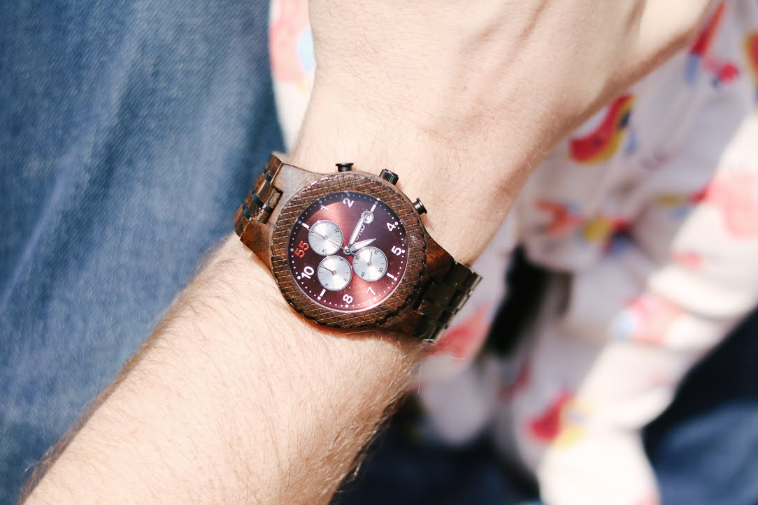 A close up of a white man's wrist wearing a dark wooden watch