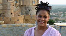 Jennifer James smiled at the camera as stands before a large stone and adobe facade, with a wide valley in the background. She has short dread locks pulled into a high ponytail, and her sunglasses pushed up on her head. She is wearing large, silver earrings, and a pink v-neck cotton blouse.