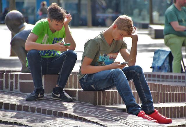 jovenes textin en el  telefono inteligente