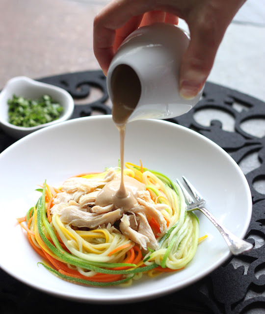 Pouring peanut sauce on Zucchini Noodles with Chicken and Tangy Peanut Sauce in a white bowl