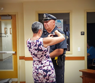 Officer Fiorio getting his badge #1 pinned by his wife