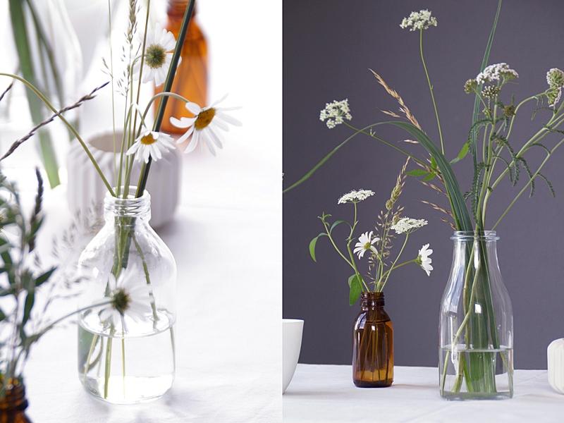 Schnelle sommerliche Tischdeko mit Margeriten, Giersch und Gräsern in Glasflaschen, Teelichtern und weißer Tischdecke | Tasteboykott