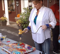 resin artist, Jane Biven, removing bubbles from resin art at a demo