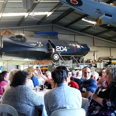 Group of people talking at a table in a hanger, with vintage airplanes suspended above.