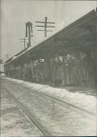 A black-and-white photograph of Dartmouth students in raccoon coats waiting on the train platform for the train to arrive.