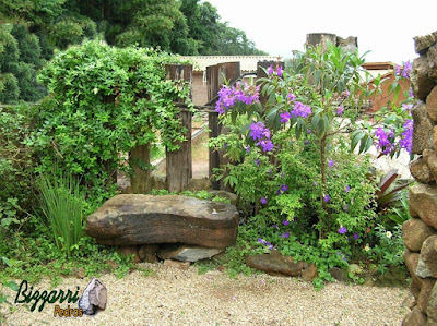 Banco de pedra no jardim, com pedra moledo, com a execução do paisagismo com o piso com pedregulho do rio com a treliça de dormente de madeira.