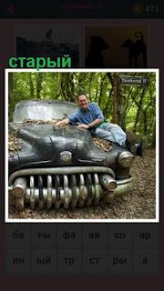 на траве стоит старый автомобиль и рядом мужчина