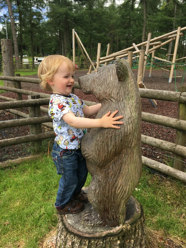Garwnant-Visitor-Centre-A-Toddler-Explores-same-picture-as-title-toddler-with-carved-bear