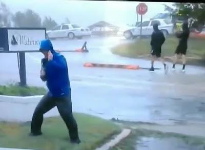 Repórter age como se o furacão Florence estivesse prestes a arrastá-lo, mas dois caras casualmente passeiam no fundo.