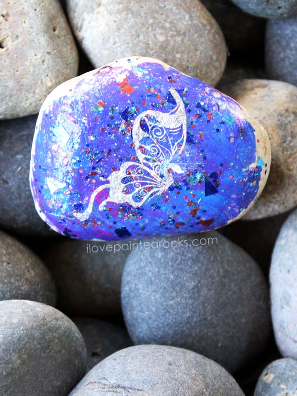 Galaxy inspired painted rock with silver butterfly