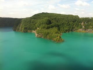 Eine Landzunge mit dichtem Wald ragt in einen türkisblauen See