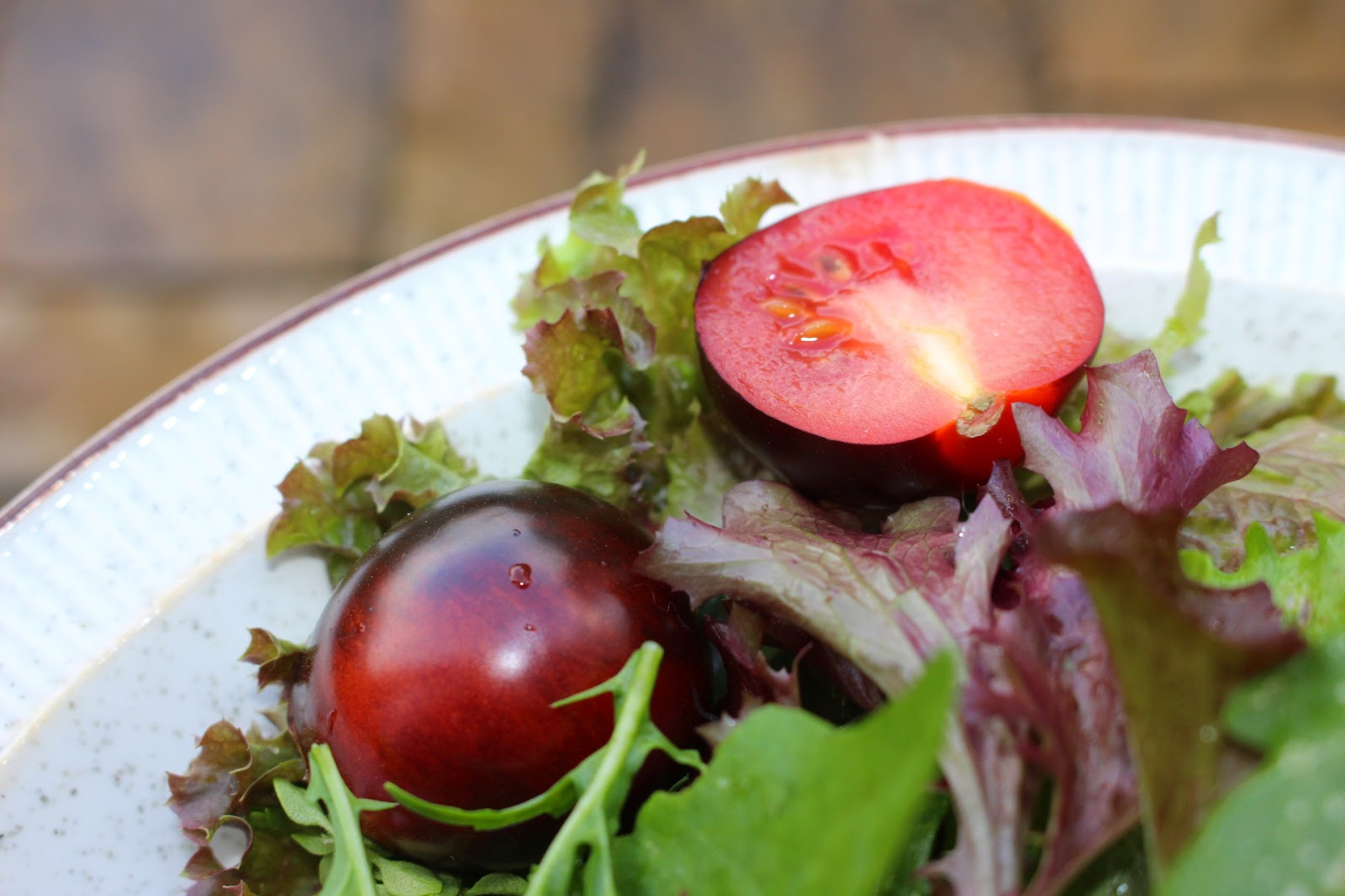 Photo of a tomato and salad leaves on a plate