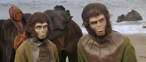Fotograma de um dos filmes originais da série Planeta dos Macacos, com um macho e uma fêmea que não faço ideia de quem sejam e um cavalo ao fundo