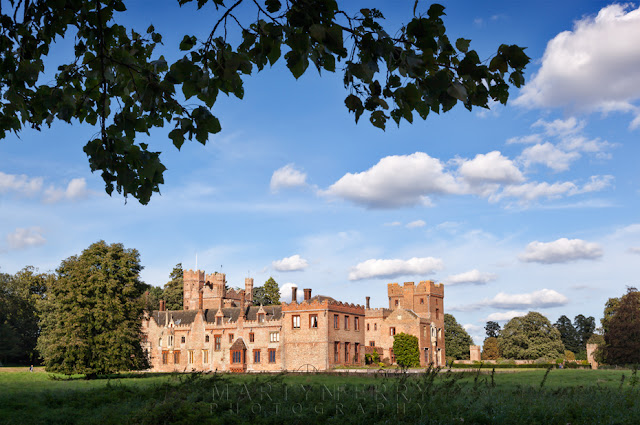 Oxburgh Hall stately home in the Norfolk countryside under a blue sky