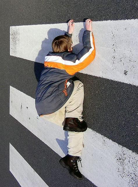 Fotoğrafın dik çekilmesiyle bir çocuk yaya geçidine tırmanıyor gibi görünüyor