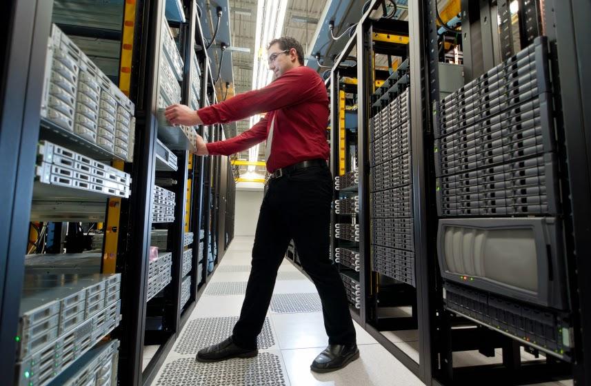 man working on servers in server room