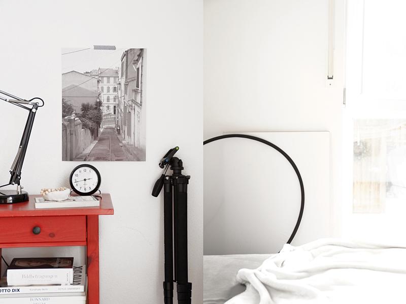 Foto in schwarz-weiß als Print drucken lassen. Schlafzimmer Nachttisch rot Ikea dekorieren schlichter skandinavisch moderner Stil, hell und reduziert. Tasteboykott.