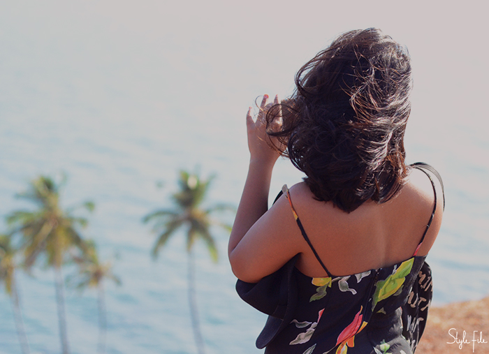 An image of a woman taking a picture on her phone of a landscape with palm trees as the wind blows her hair