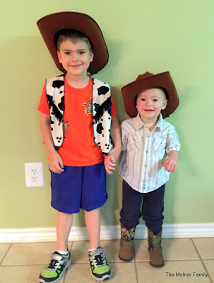 Andrew wearing blue athletic shorts, an orange shirt, a cow print vest and cowboy hat and holding hands with Benjamin wearing boots, jeans, a pearl snap shirt and cowboy hat.