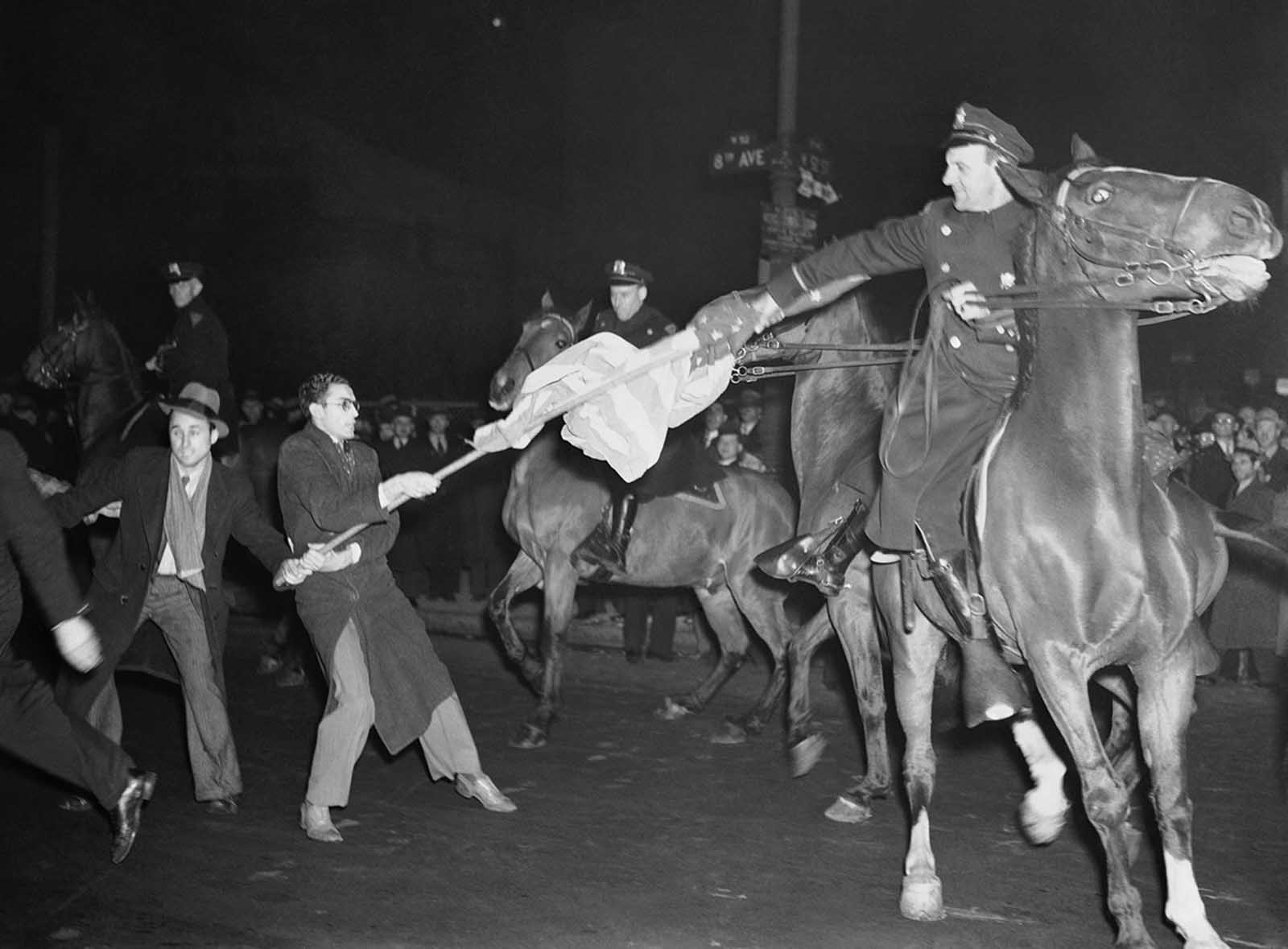 A New York City mounted policeman outside Madison Square Garden at 50th Street and 8th Avenue during a German American Bund meeting, is shown attempting to take an American flag away from one of the demonstrators who marched outside carrying the staff and banner on February 20, 1939.