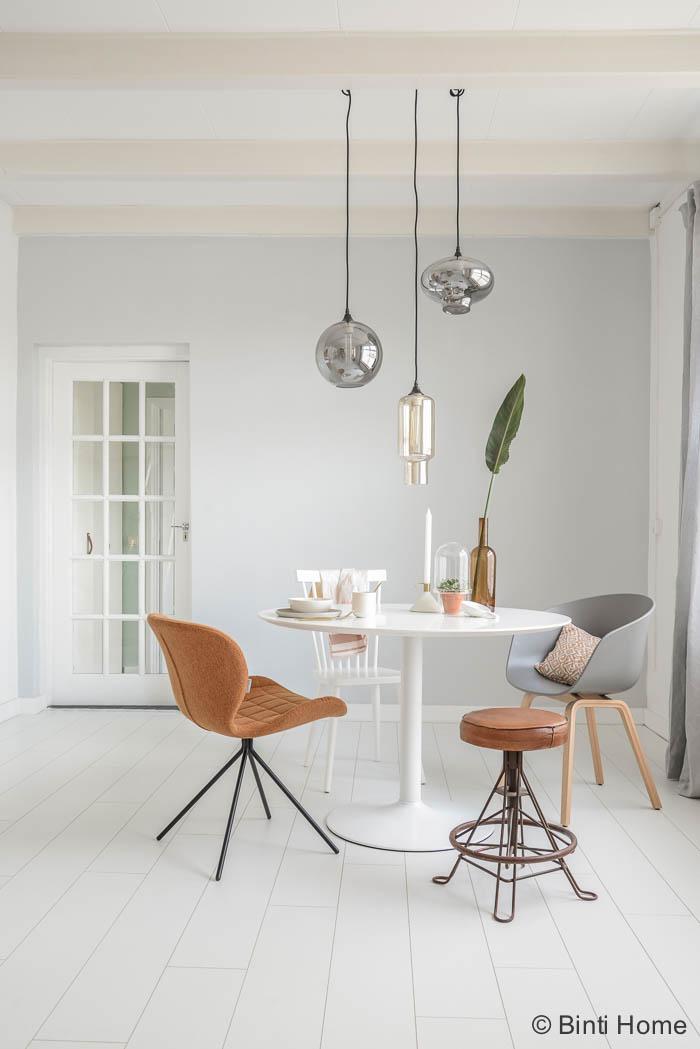 Een doorkijk naar de ronde tafel en een mix van stoelen