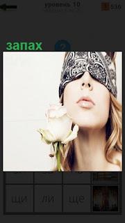 Девушка с завязанными глазами изучает запах идущий от цветка в руке