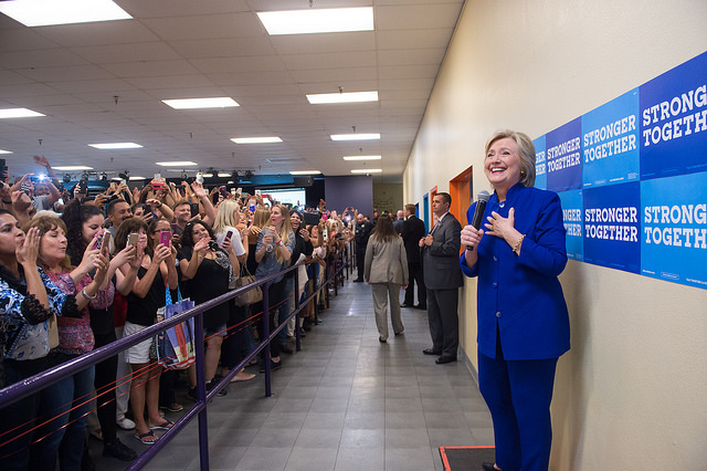 image of Hillary Clinton standing on a box in front of a large, excited crowd; she is holding a microphone and smiling broadly, her hand clasped to her heart