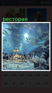 под водой ресторан и над головами посетителей плавают рыбы