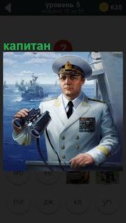 На мостике стоит капитан в форме и с биноклем в руках, в фуражке
