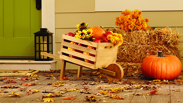 Front porch decorated for Fall - pumpkins, green door, lantern, hay bales, leaves on the floor