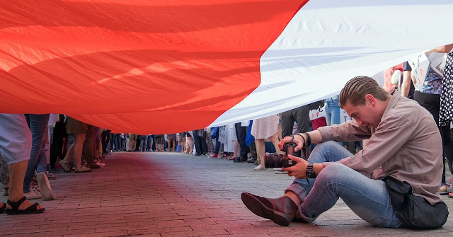 Young man, photographer, under a big Polish flag, on the street.
