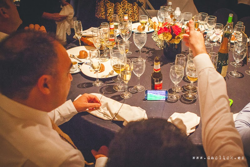invitados ven el partido de futbol en el móvil mientras se celebra el banquete