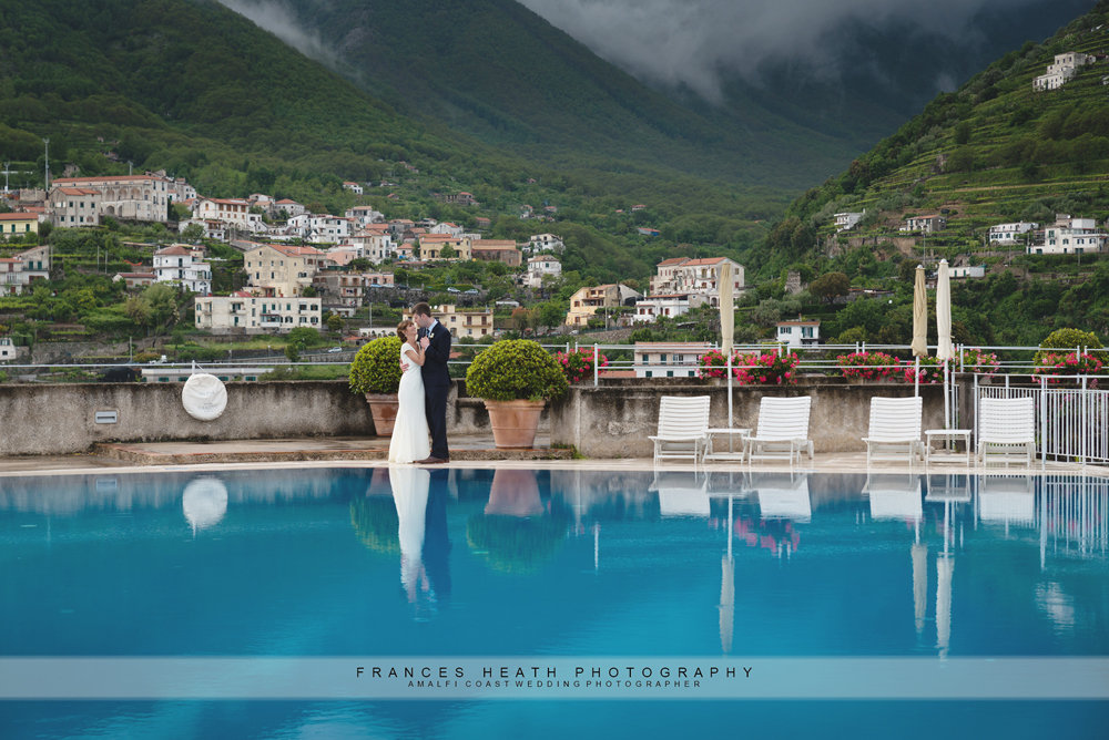 Bride and groom reflected in infinity pool