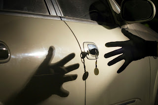 Gloved hand reaching for vehicle key in door