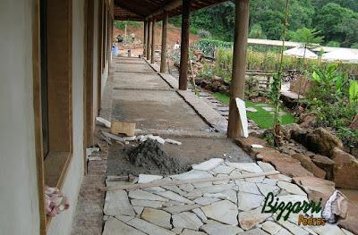 Execução dos pisos do terraço com os pilares de madeira, com as soleiras de pedra folheta e com o piso com cacos de pedra São Tomé.
