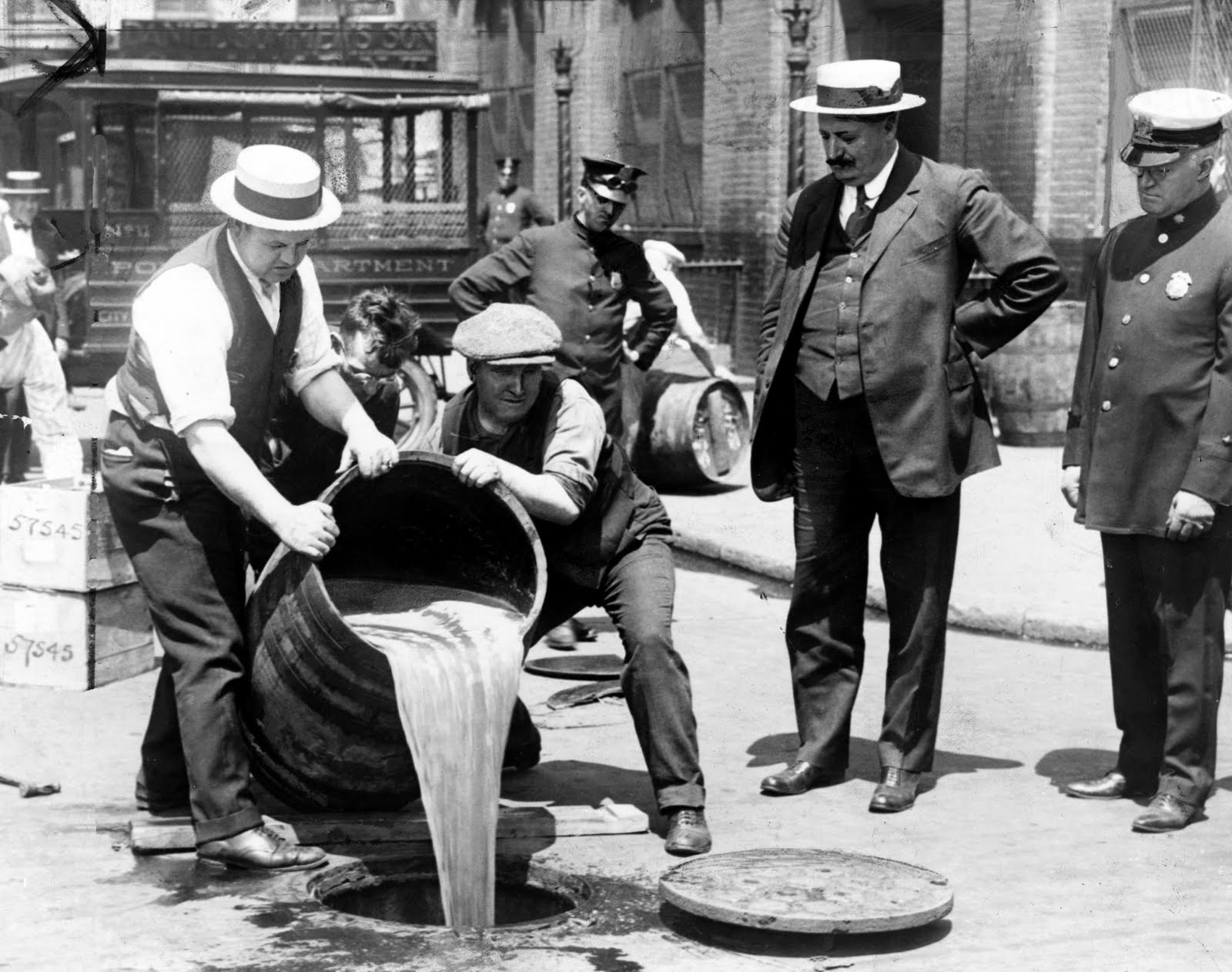 Police pour liquor into sewer following a raid during prohibition
