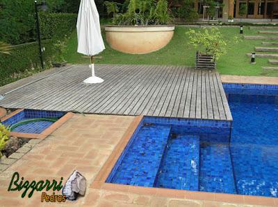 Detalhe do deck de madeira na piscina com a escada interna na piscina com o revestimento com pastilha azul, no piso do passeio da piscina o piso de tijolo com as bordas com cerâmica e em volta do piso de tijolo a soleira de pedra paralelepípedo.