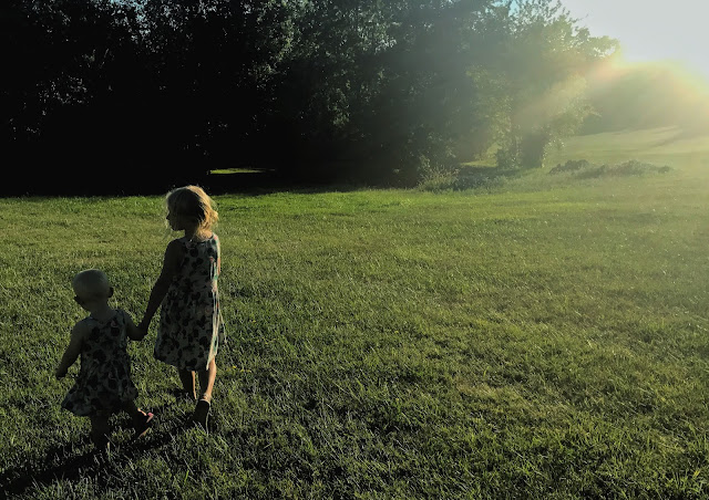 Two young girls walking hand in hand away from the camera partially silhouetted by the setting sun