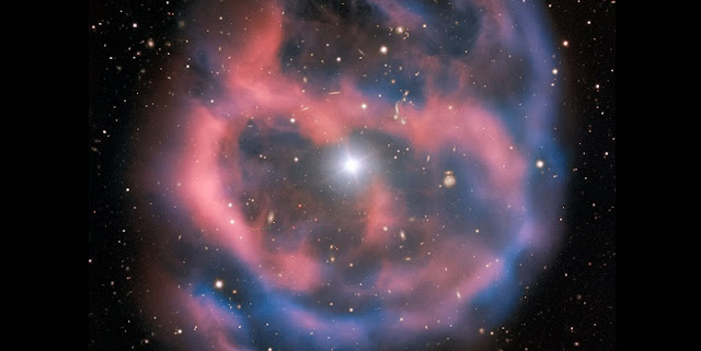 The faint, ephemeral glow emanating from the planetary nebula ESO 577-24 persists for only a short time  — around 10,000 years, a blink of an eye in astronomical terms. ESO's Very Large Telescope captured this shell of glowing ionised gas — the last breath of the dying star whose simmering remains are visible at the heart of this image. As the gaseous shell of this planetary nebula expands and grows dimmer, it will slowly disappear from sight.  This stunning planetary nebula was imaged by one of the VLT's most versatile instruments, FORS2. The instrument captured the bright, central star, Abell 36, as well as the surrounding planetary nebula. The red and blue portions of this image correspond to optical emission at red and blue wavelengths, respectively.  An object much closer to home is also visible in this image — an asteroid wandering across the field of view has left a faint track below and to the left of the central star. And in the far distance behind the nebula a glittering host of background galaxies can be seen.  Credit: ESO