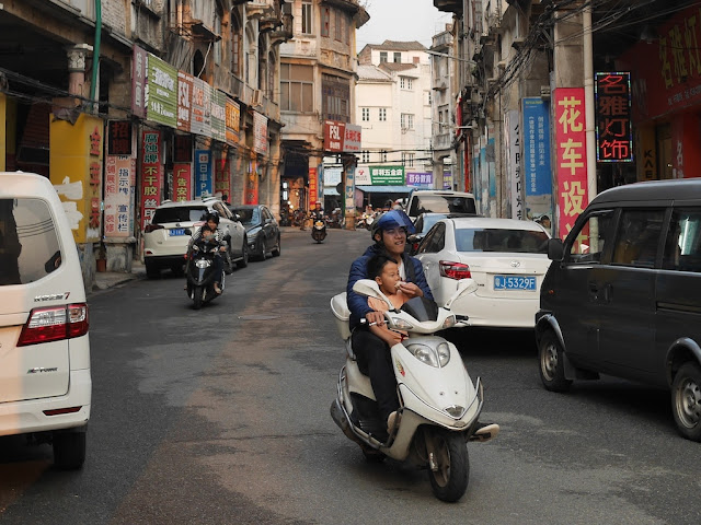 man feeding a boy a snack while they ride a motor scooter