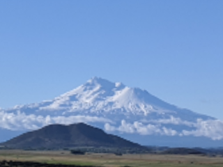 View of Mount Shasta against a bright blue sky.