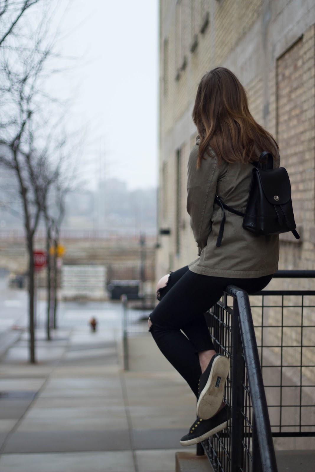 バックパックを背負って階段の手摺に座った女性の後ろ姿