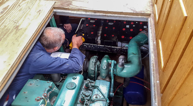 Photo of Phil and John checking the bank of batteries on board