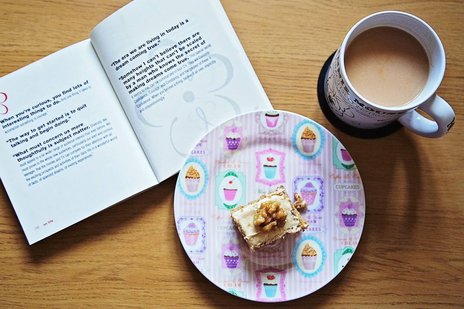Piece of coffee and walnut traybake with cup of tea and a book.
