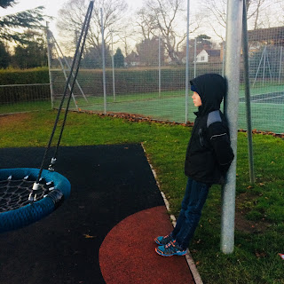 Autistic boy leans on a swing in a cold playground - when medication costs
