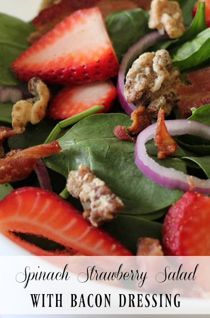 This spinach salad is topped with fresh strawberries, red onions, candied nuts, and a hot bacon dressing you won't get enough of!