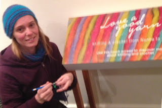 A blurry photograph of Jodie crocheting next to the Love a Good Yarn title display. Jodie is wearing a beanie and scarf in turquoise, purple, aqua and plum colours with a plum hooded jacket.